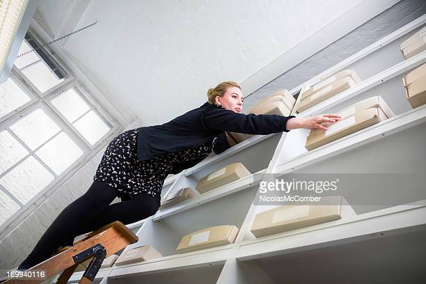woman on a ladder reaching for a box out of reach - hazard stock pictures, royalty-free photos & images