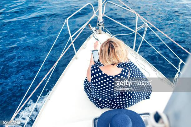 Woman on a luxury yacht looking at a smartphone