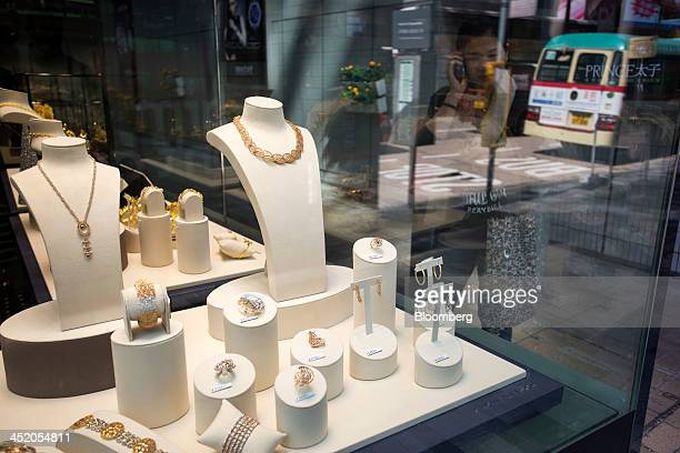A woman on a mobile device looks at gold jewelry displayed in the window of a Chow Tai Fook Jewellery Group Ltd store in the shopping district of...