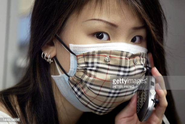 A woman on a mobile phone wears a Burberry Check mask to protect against a killer outbreak of pneumonia which shows no sign of abatting in the...