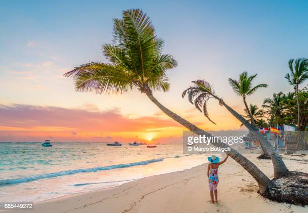 Woman on a palm fringed beach at sunrise. Dominican Republic.