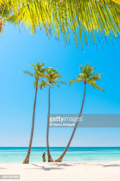 Woman on a palm fringed beach. Playa Juanillo, Dominican Republic.