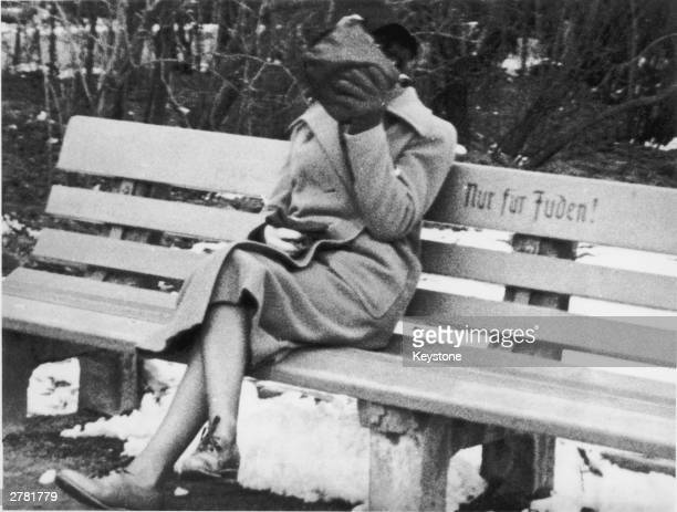 Woman on a park bench in Nazi Germany hides her face behind her handbag, circa 1938. The bench is marked 'Nur Fur Juden' .