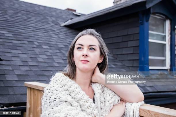 woman on a porch wrapped in a blanket - capelli grigi foto e immagini stock