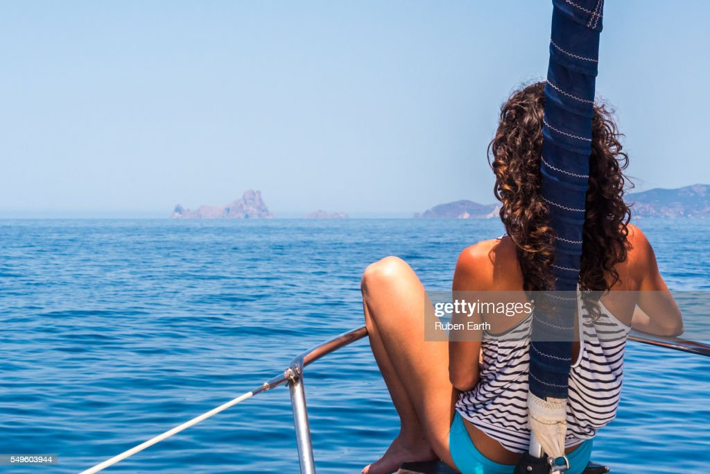 Woman on a sailboat arriving to Es Vedra Island : Stock Photo