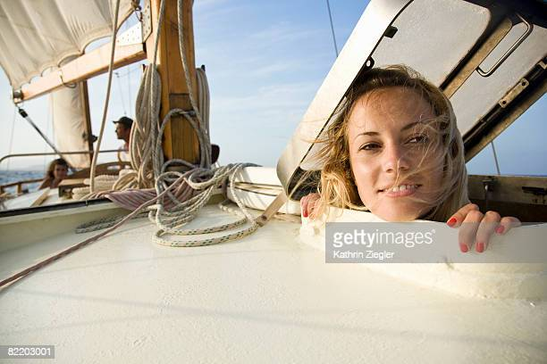 woman on a sailing boat, looking out the hatch