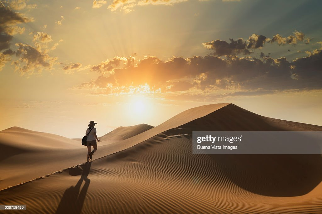 Woman on a sand dune at sunset : ストックフォト