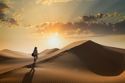 Woman on a sand dune at sunset - gettyimageskorea