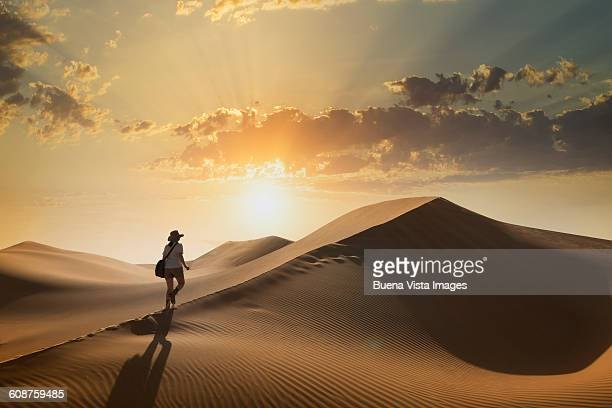 woman on a sand dune at sunset - avontuur stockfoto's en -beelden