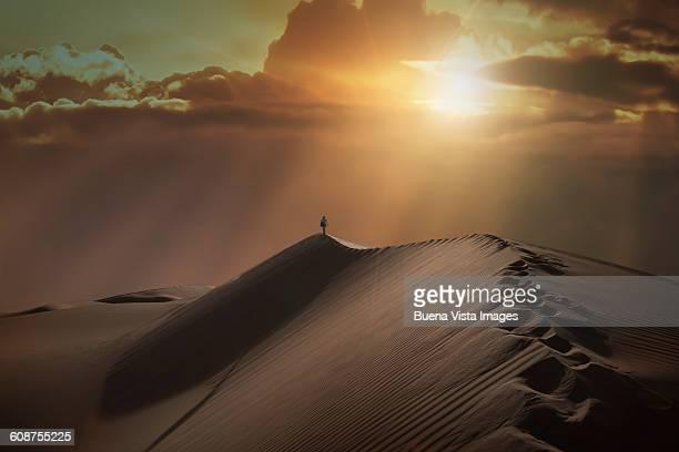 woman on a sand dune - paisajes de emiratos arabes fotografías e imágenes de stock