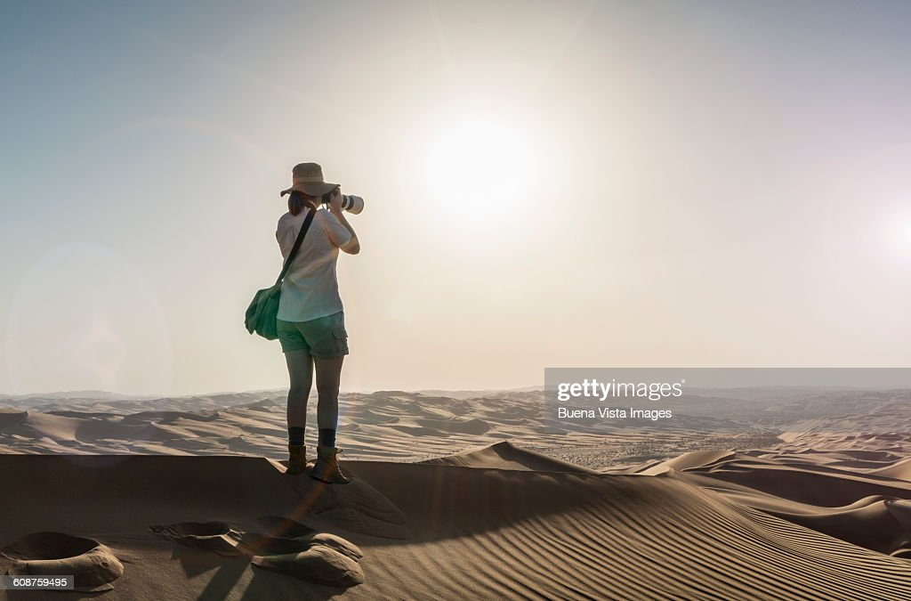 Woman on a sand dune taking pictures of sunset : Stock Photo