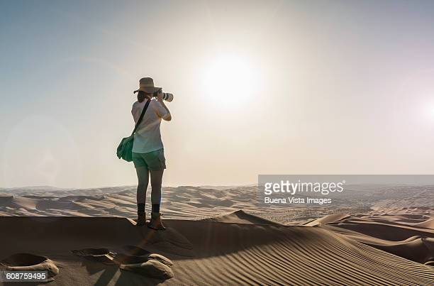 Woman on a sand dune taking pictures of sunset