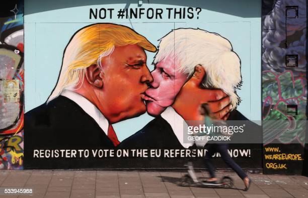 A woman on a scooter passes a mural showing likely US Republican presidential nominee Donald Trump kissing the Former Mayor of London and...