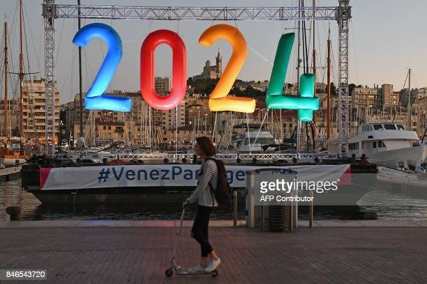 A woman on a scooter rides past an inflatable '2024' logo in the old harbour area of Marseille late September 13 during celebrations after the...