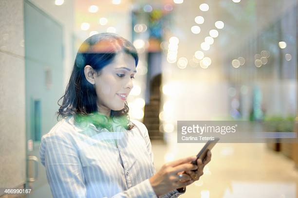 Woman on a smart phone taken through glass