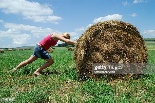 Woman on a South African Farm Pushing a Round Hay Bail in Pasture