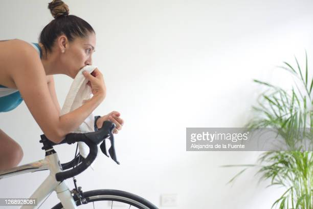 woman on a stationary bike. - peloton stock pictures, royalty-free photos & images
