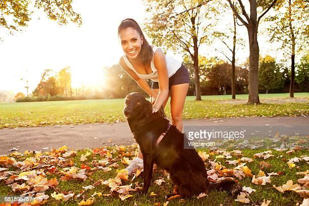 woman on a stroll with her dog in autumn - alleen één mid volwassen vrouw stockfoto's en -beelden
