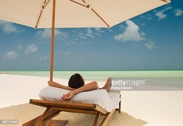 Woman on a sunlounger on a tropical beach.