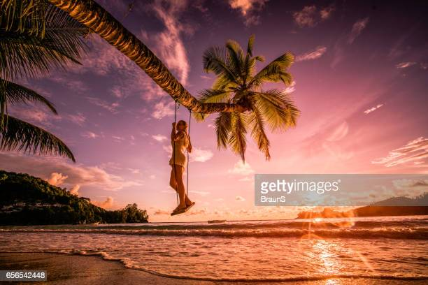 Woman on a swing above the sea at sunset beach.