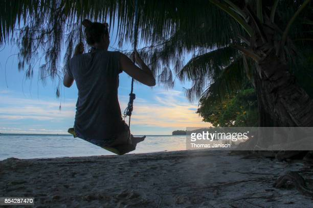 Woman on a swing at the beach during sunset, Palau