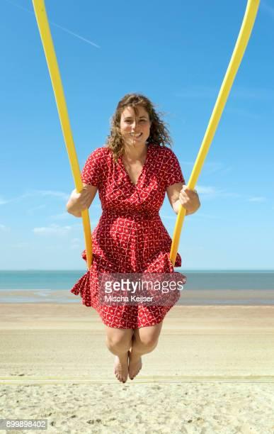 Woman on a swing on a beach, Zoutelande, Zeeland, Netherlands, Europe