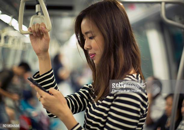Woman on a train looking at her phone.