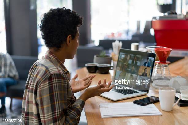 woman on a video conference at a coffee shop - middelgrote groep mensen stockfoto's en -beelden