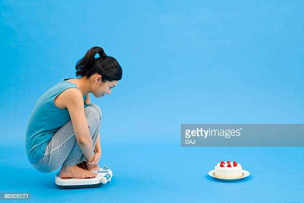 Woman on a weight scale looking at cake
