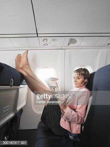Woman On Aeroplane Reading Newspaper Resting Feet On Chair