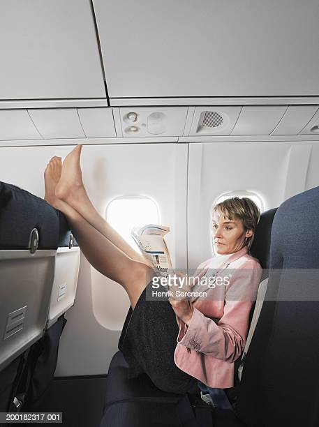 Woman on aeroplane reading newspaper, resting feet on chair in front
