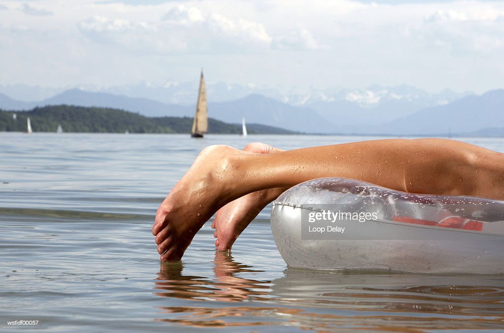 Woman on air mattress, lying on front, Lake Starnberg, Bavaria, Germany : Foto de stock