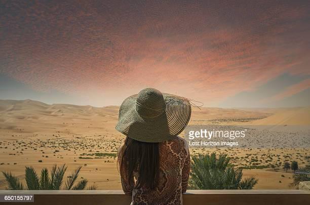 Woman on balcony, looking at desert view, at sunset, rear view, Abu Dhabi, Abu Dhabi Emirate, UAE