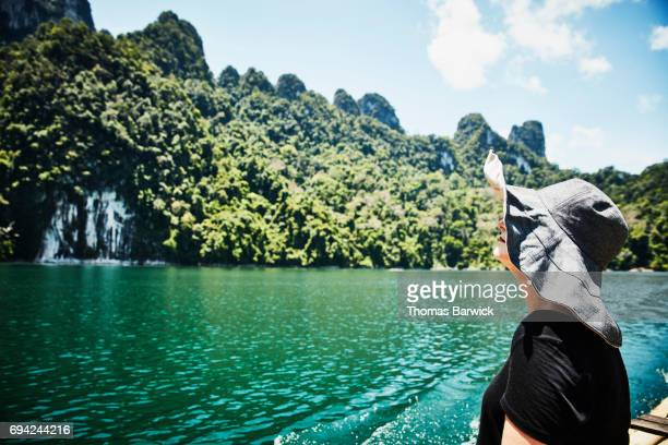 Woman on bamboo raft looking at limestone cliffs in Khao Sok National Park Thailand