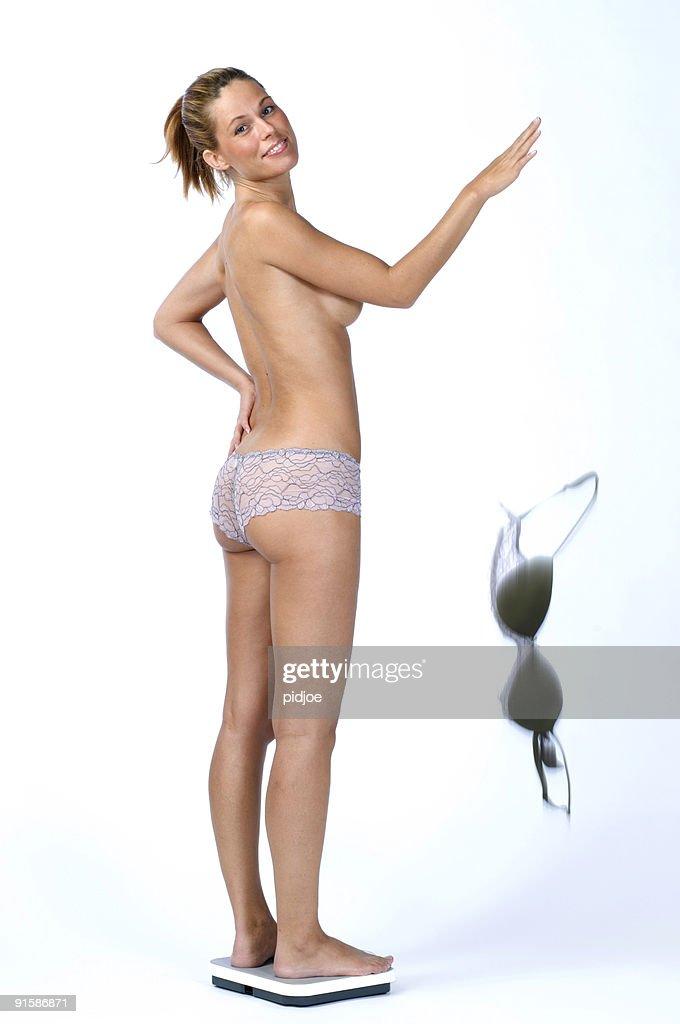 woman on bathroom scale dropping bra : Stock Photo