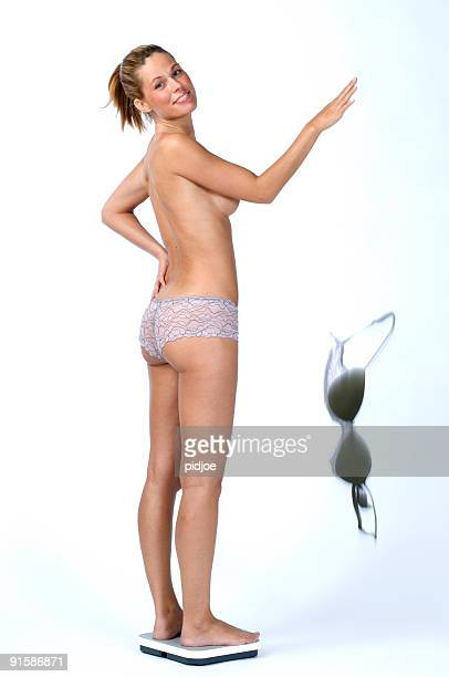 woman on bathroom scale dropping bra - women in slips stock photos and pictures
