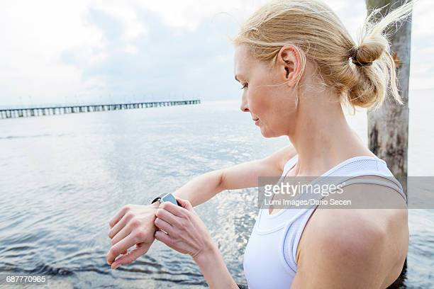 Woman on beach checking running watch