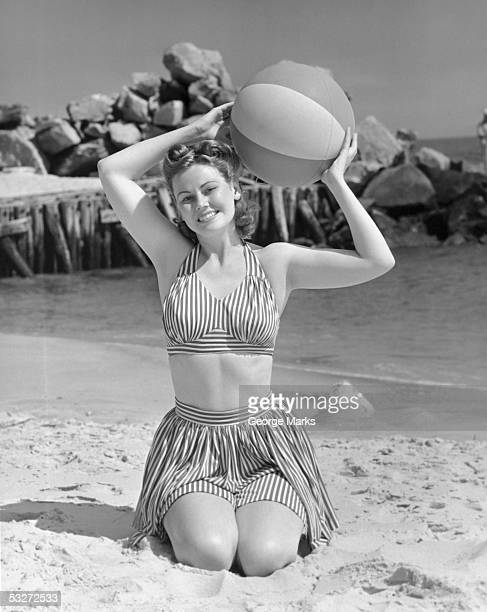 Woman on beach holding beach ball