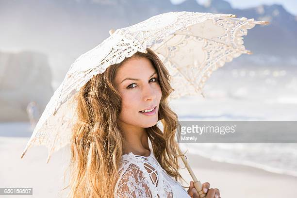 Woman on beach holding lace umbrella looking at camera smiling