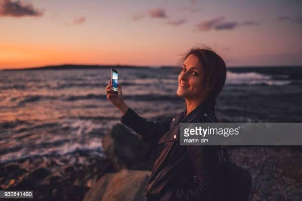 woman on beach holiday photographing the sunset - mensagem com foto imagens e fotografias de stock