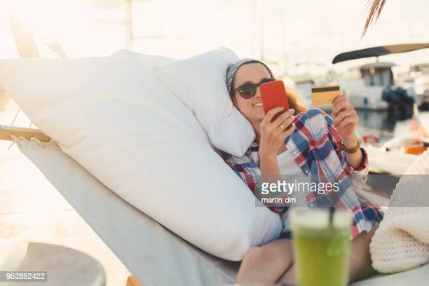 Woman on beach holiday relaxing in hammock and shopping online with credit card