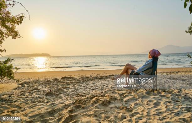 Woman on beach in deckchair looking away at sea, Florianopolis, Santa Catarina, Brazil, South America