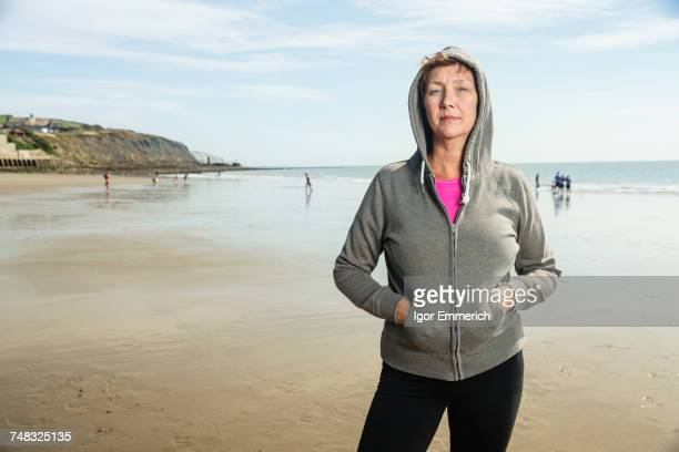 Woman on beach in hooded top, Folkestone, UK