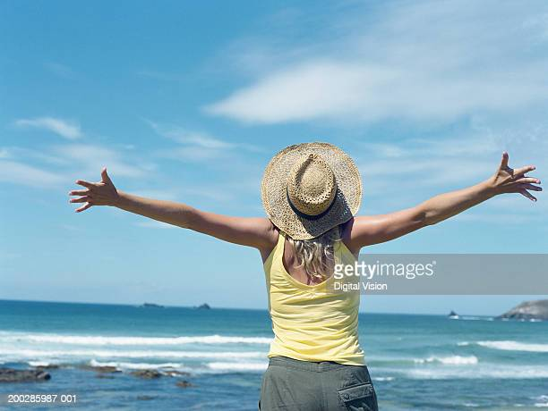 Woman on beach in straw hat, head back, arms outstretched, rear view