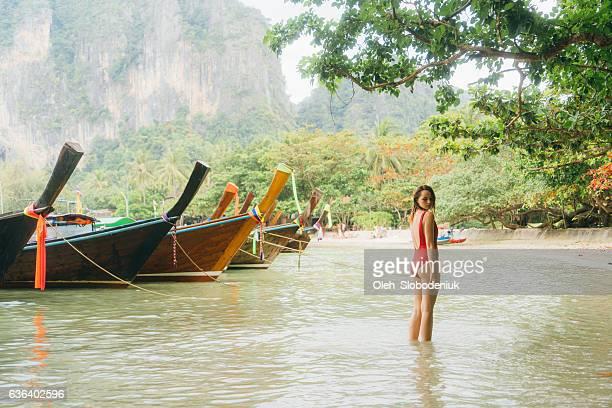 frau am strand in thailand - asiatisches langboot stock-fotos und bilder