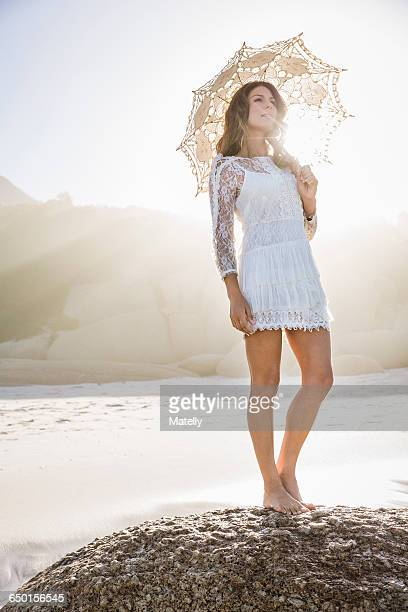 woman on beach standing on rock wearing short white dress holding umbrella, looking away - mini dress stock pictures, royalty-free photos & images