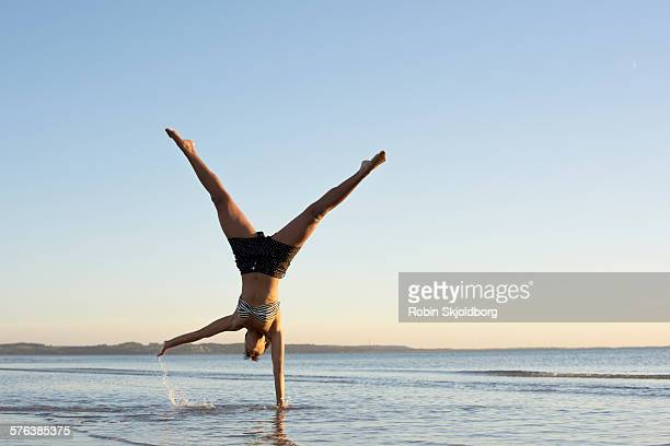 Woman on beach turning cartwheels