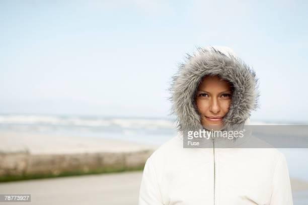 woman on beach wearing parka - フード付きコート ストックフォトと画像