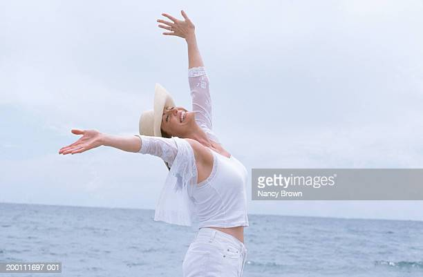 woman on beach with arms up smiling, side view - 前をはだけた ストックフォトと画像