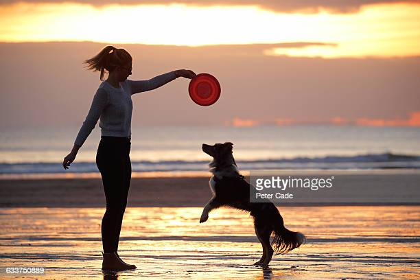Woman on beach with dog at sunset